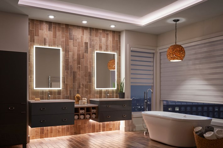 A bathroom featuring two types of accent lighting: cove lighting and lighting under the vanity. The other layers of light include edge lit mirrors, recessed lighting over the vanity, and a pendant over the tub.