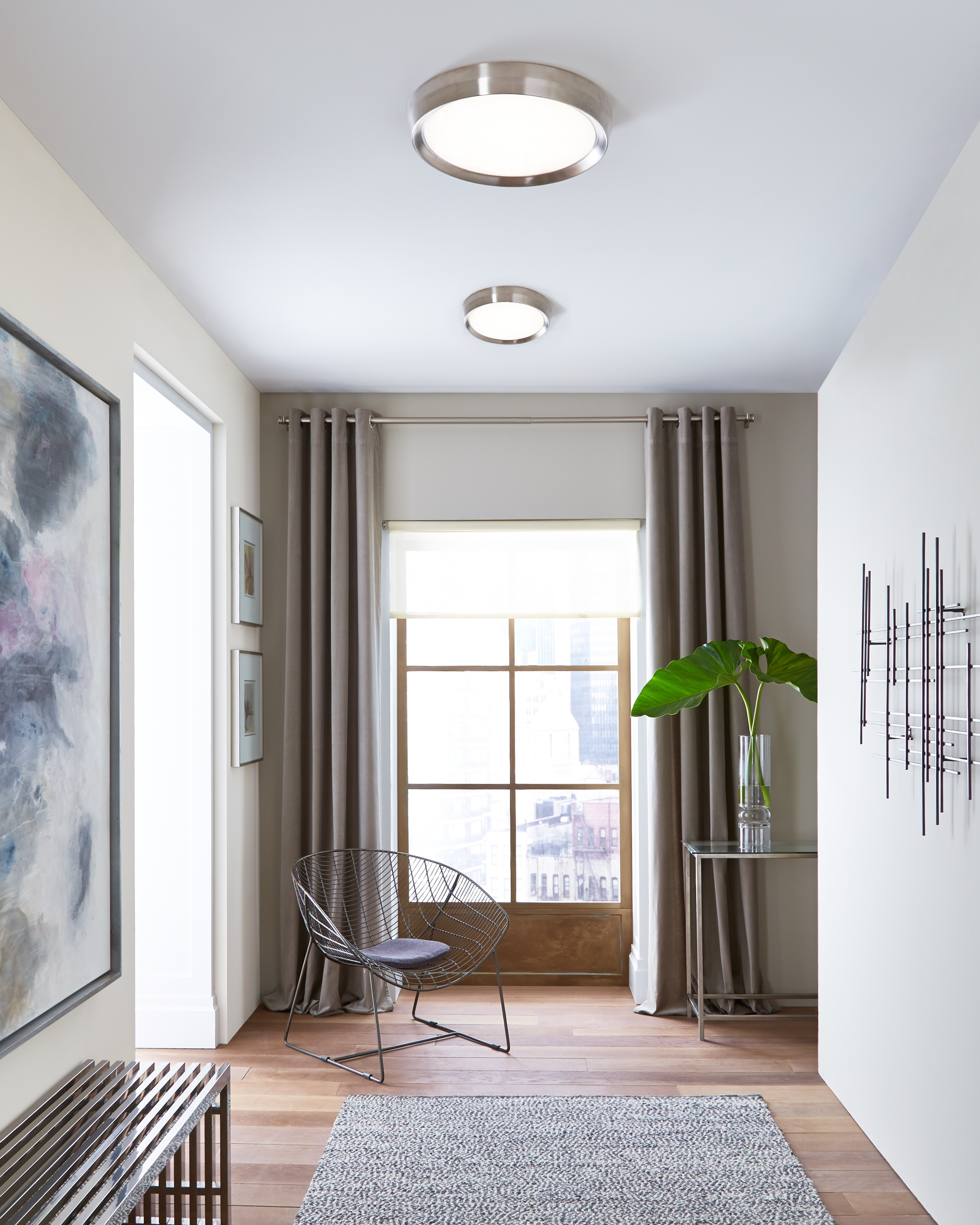 This Tech Lighting flush mount illuminates and adds to the decor of this foyer.