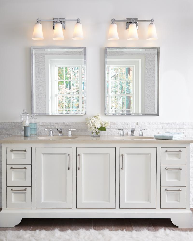 Showing a two sink vanity with a bath sconce over each mirror. Murray Feiss VS23703 Monterro Collecion 3 Light Vanity in Chrome.