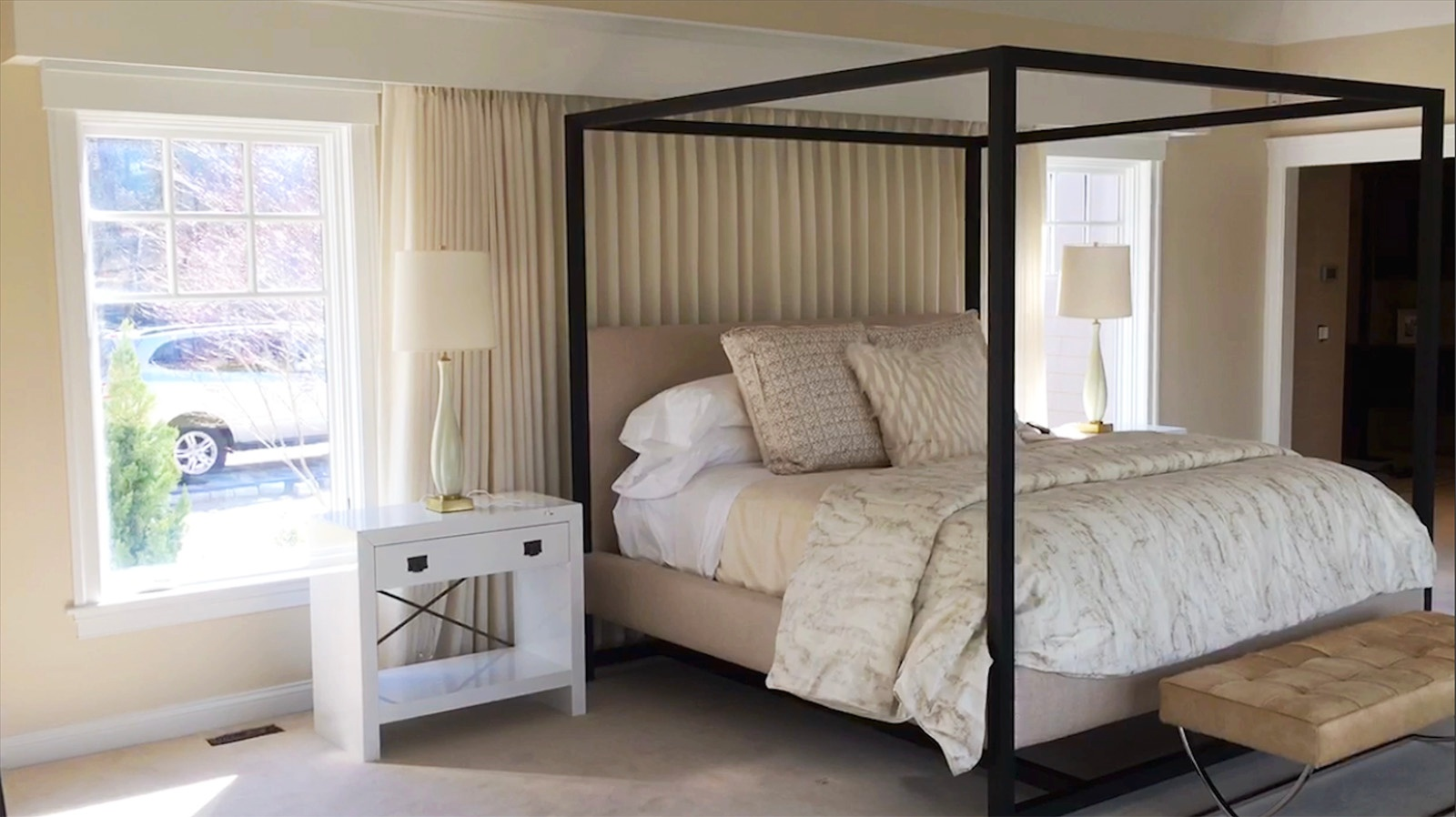 A sunny master bedroom with motorized drapes and room darkening roller shades for light control.